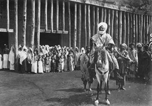 Le Sultan à cheval. Ses femmes au second plan